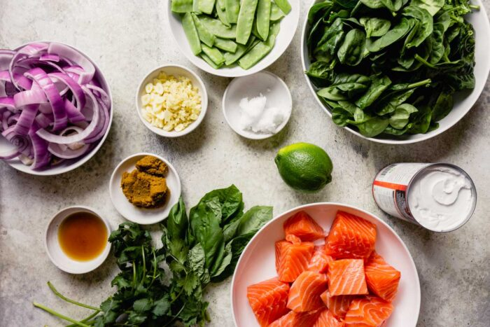 overhead image of ingredients mise en placed in white bowls; including raw chunks of salmon, spinach, garlic, ginger, basil, cilantro, a lime, snow peas, red onions, curry paste and fish sauce