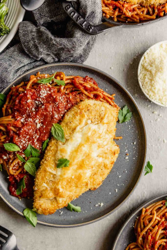 gray plate topped with spaghetti and tomato sauce and breaded chicken topped with cheese