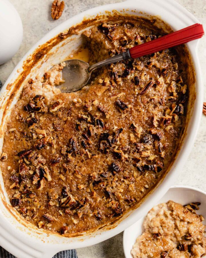 baking dish filled with a sugary baked oatmeal with a red handled spoon set in the dish and oatmeal in a small white bowl off to the side