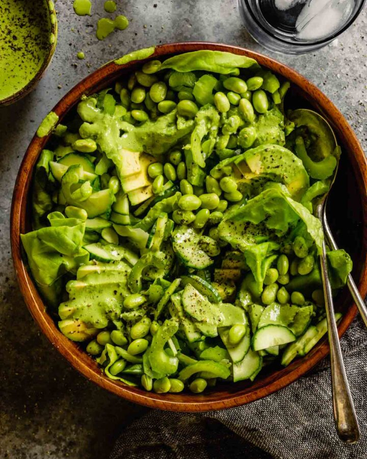 lettuce greens and vegetables in a brown bowl set on a gray table