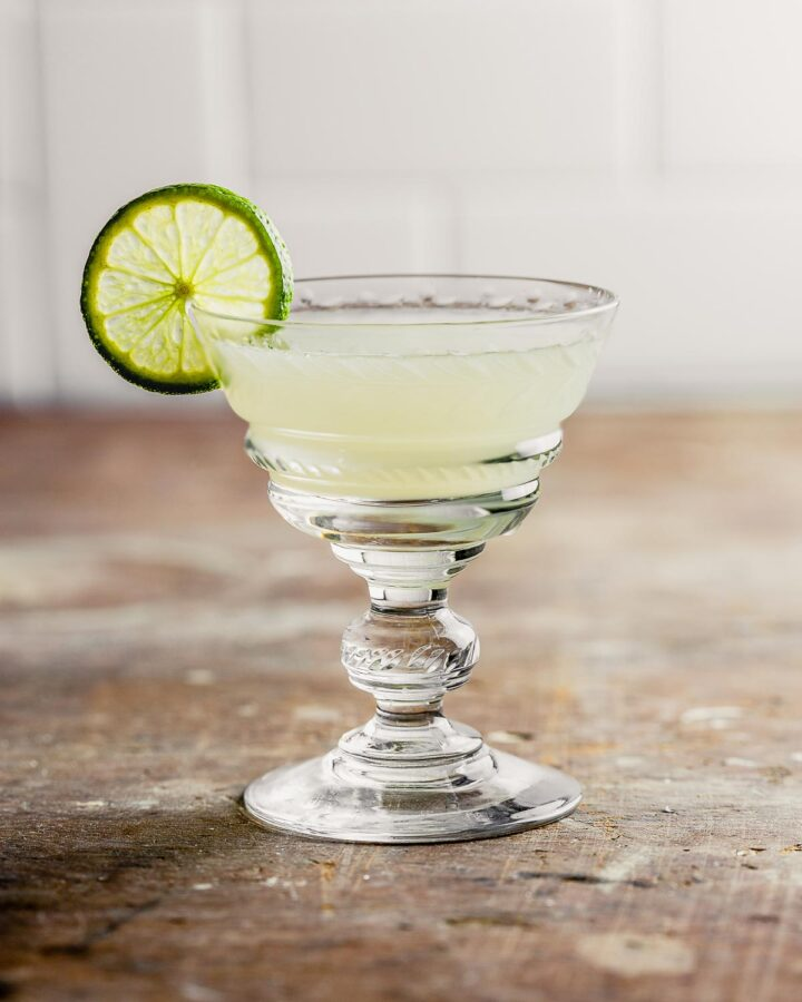 yellow cocktail in a coupe glass set on a wood table with a like wheel garnished on glass